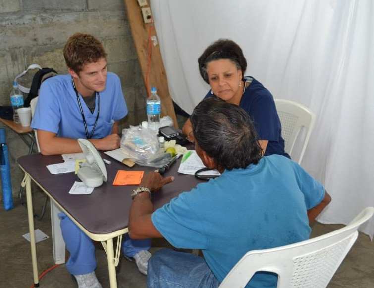 2 medical people talking to a patient