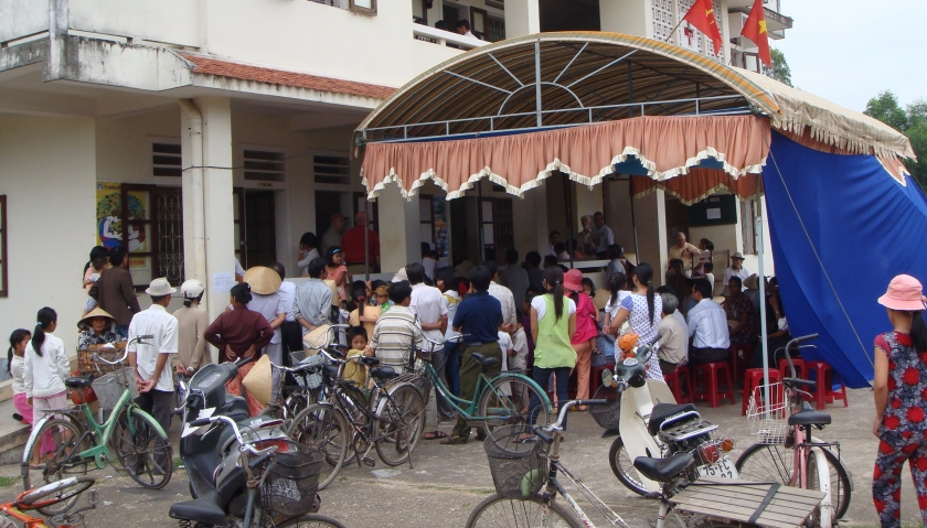 Vietnamese people with bicycles, standing outside a clinic