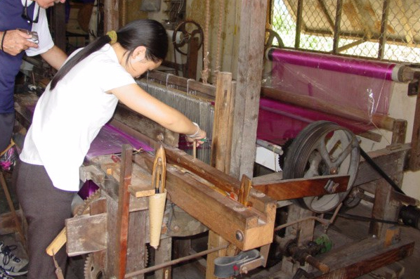 Asian woman working on a large loom