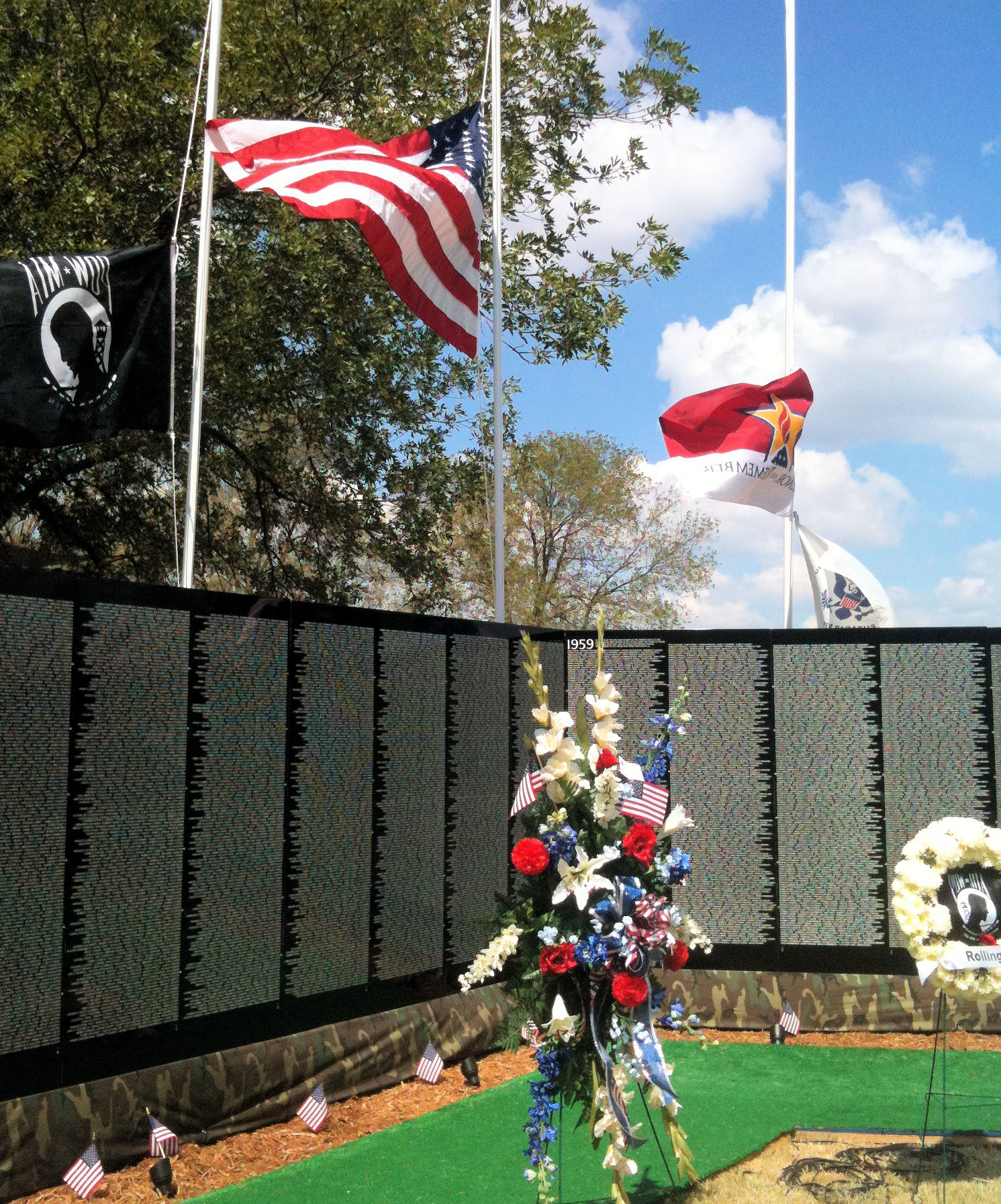 a replica of the Vietnam Memorial Wall with an American flag and a wreath of red, white, and blue flowers