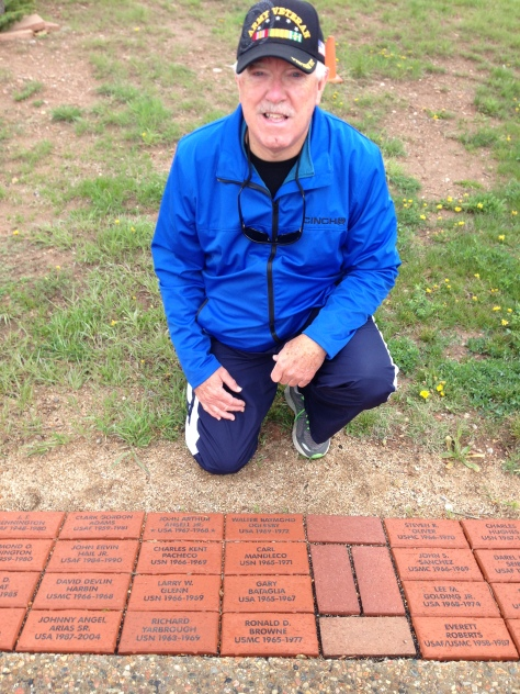 Army veteran kneeling by inscribed bricks