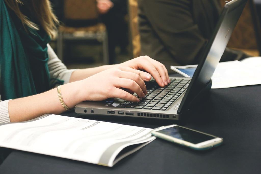 woman typing on a laptop keyboard.