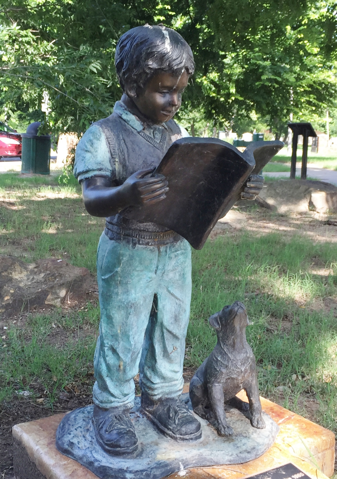 statue of boy reading a book