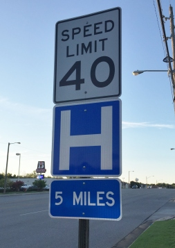 a speed limit sign with an H for hospital , 5 miles