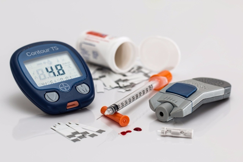 a glucometer and insulin syringe