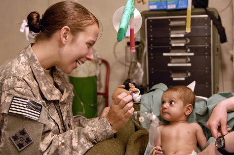 a female military doctor examining a child