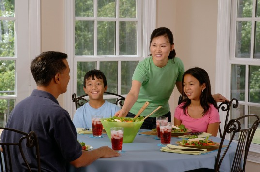 Family of 4 sitting at a dining table.