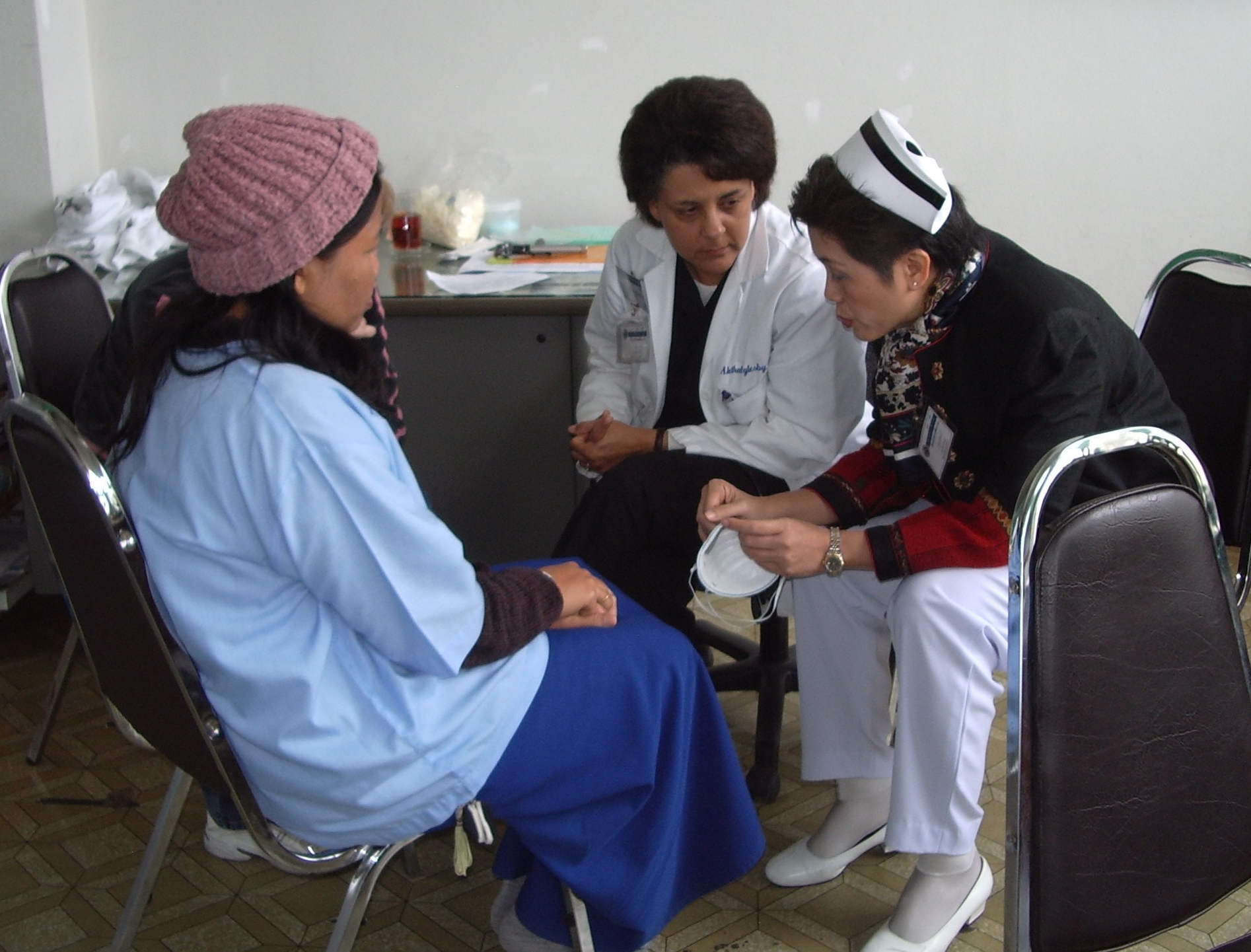 a doctor and nurse talk to a patient in an Asian country.