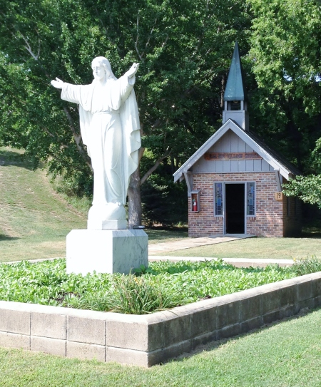 a statue of Christ and a small church
