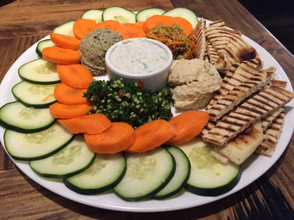 healthy plate of vegetables , pita bread and hummus