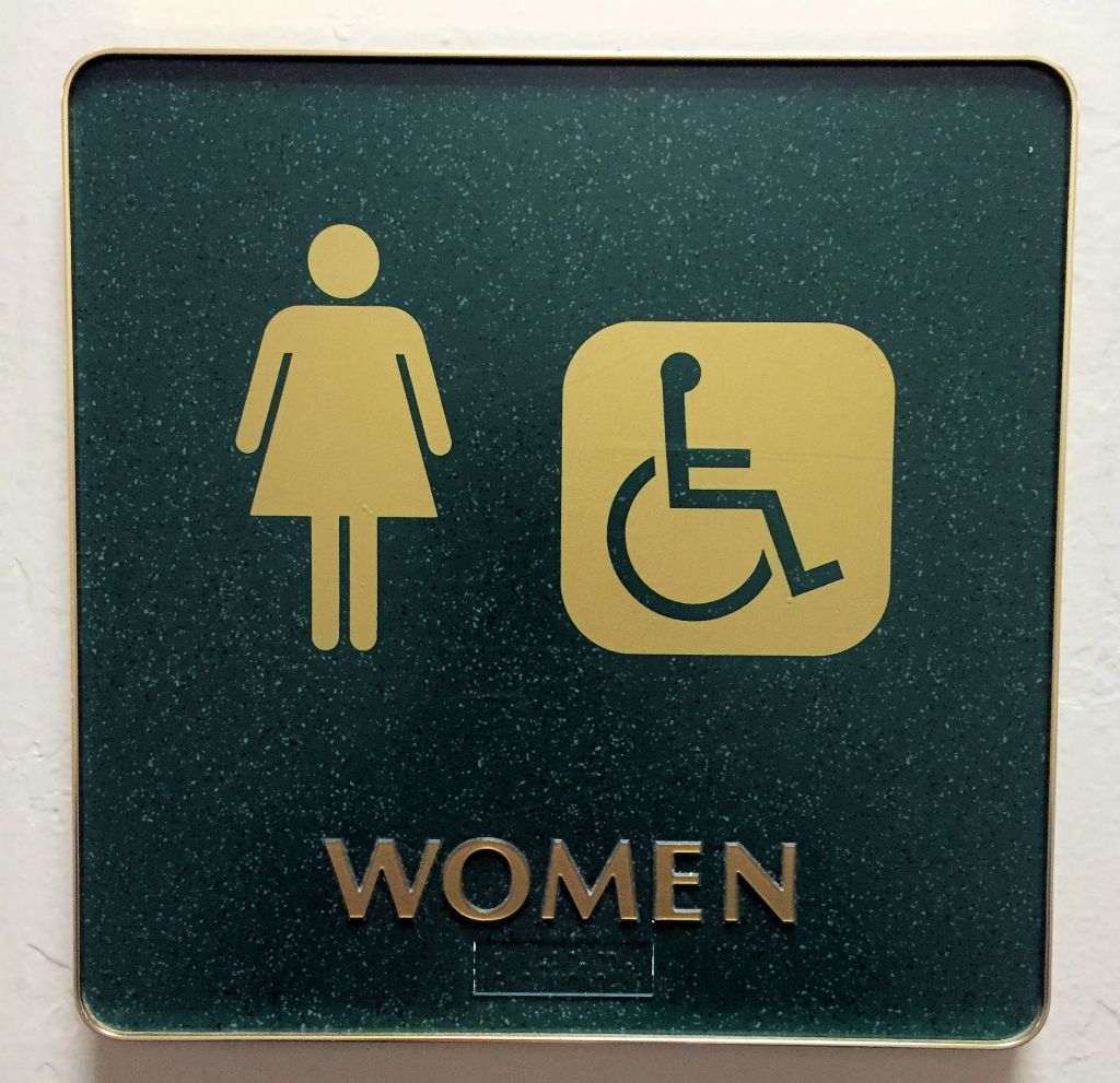 WOMEN- a restroom sign with a female figure and a wheelchair drawing