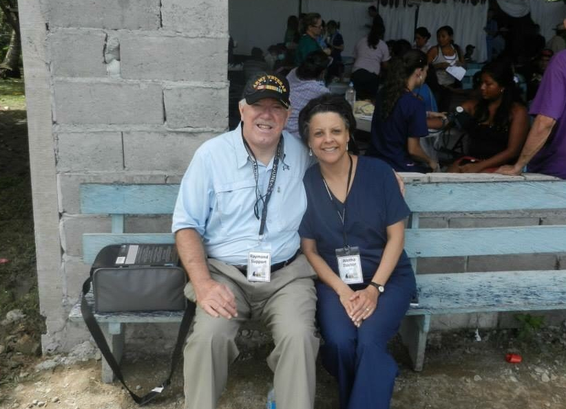 a woman in a medical scrub suit and man with army veteran cap, in a rural setting