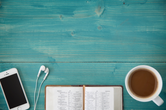 an open Bible, a phone with ear buds, a cup of coffee