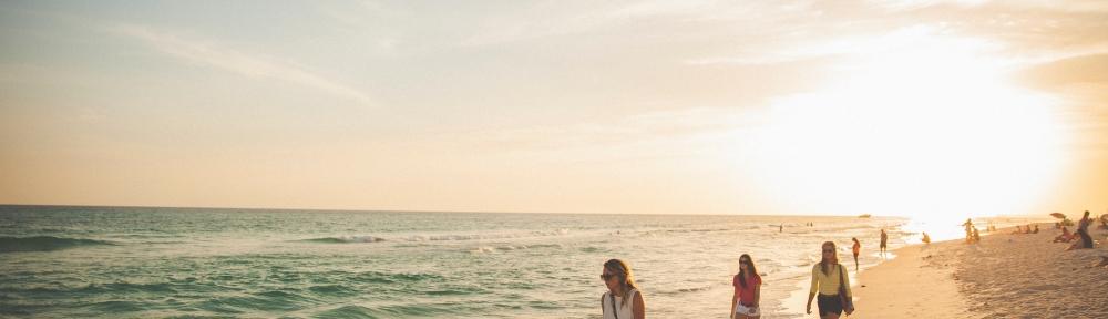 a beach with women walking along the shore