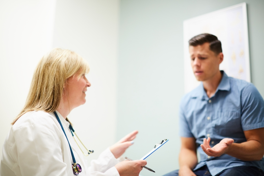 a female physician talking to a male patient