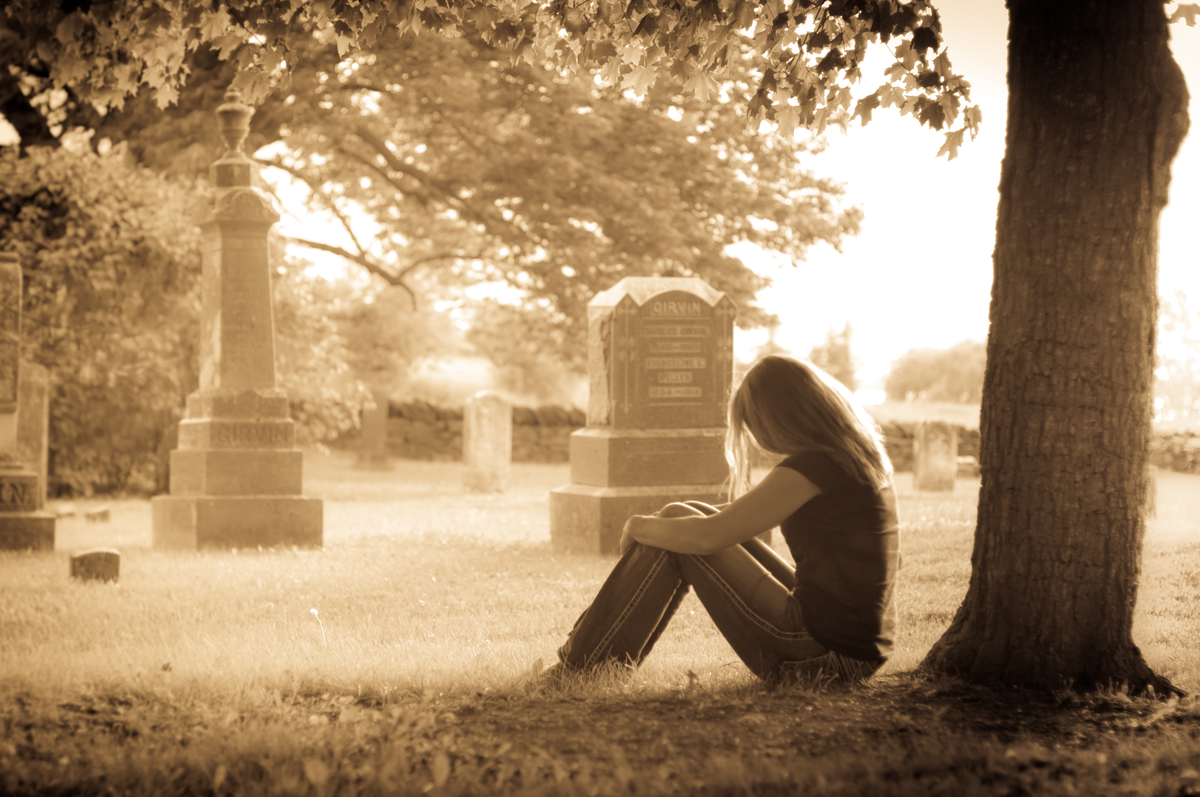 woman sitting in a cemetery