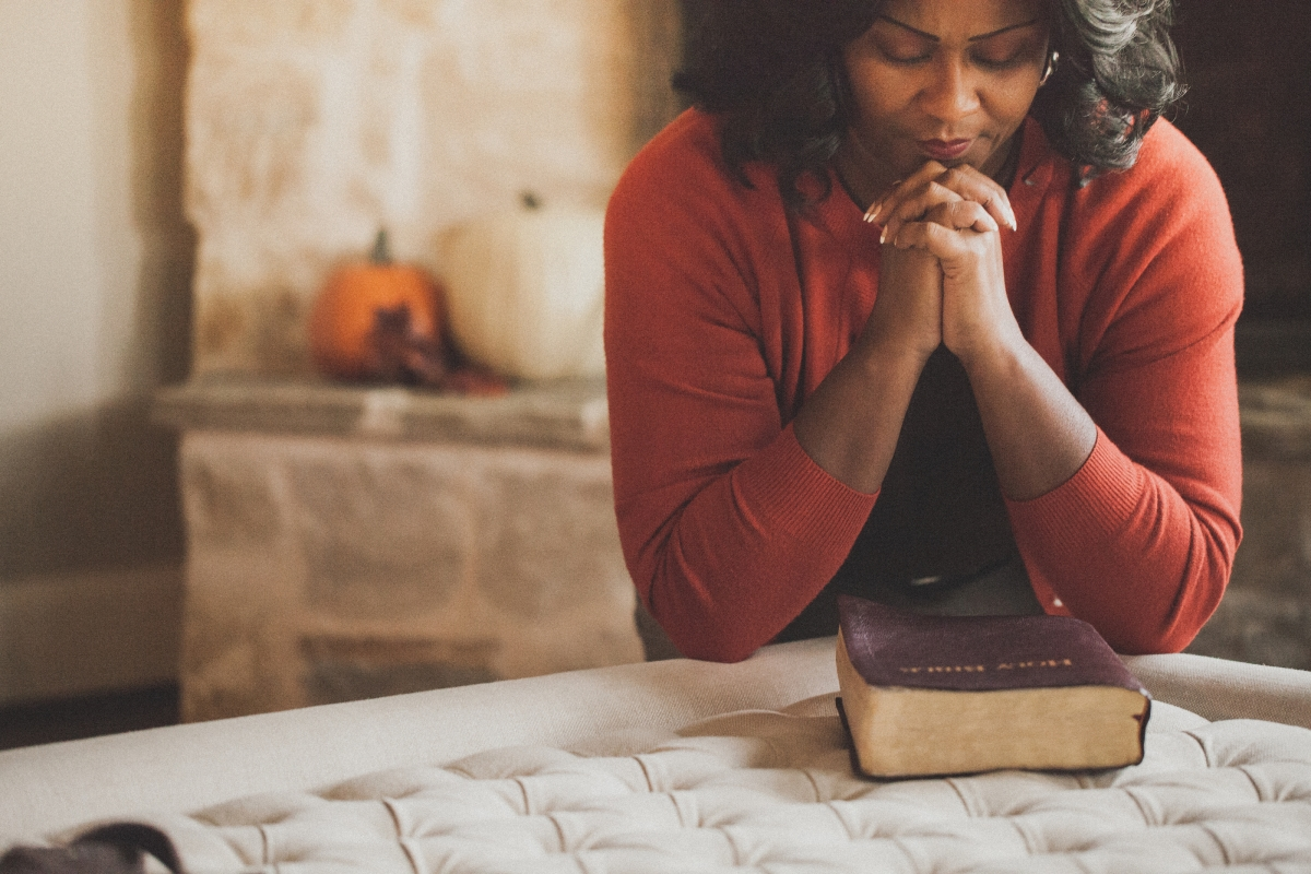 a women with hands clasped in prayer with a Bible
