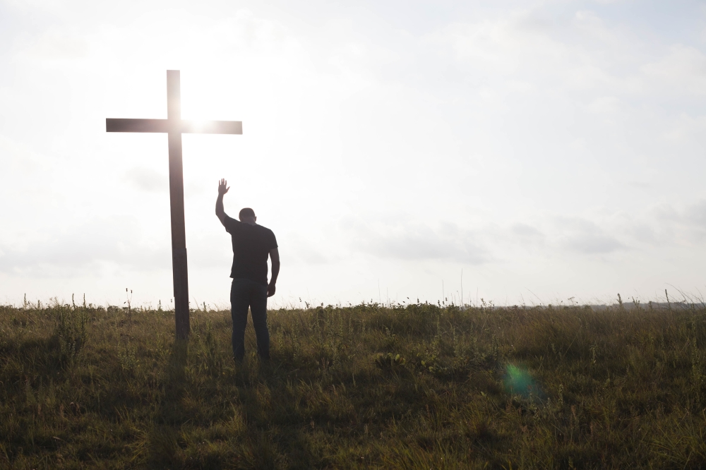 man standing in front of a cross with one arm raised