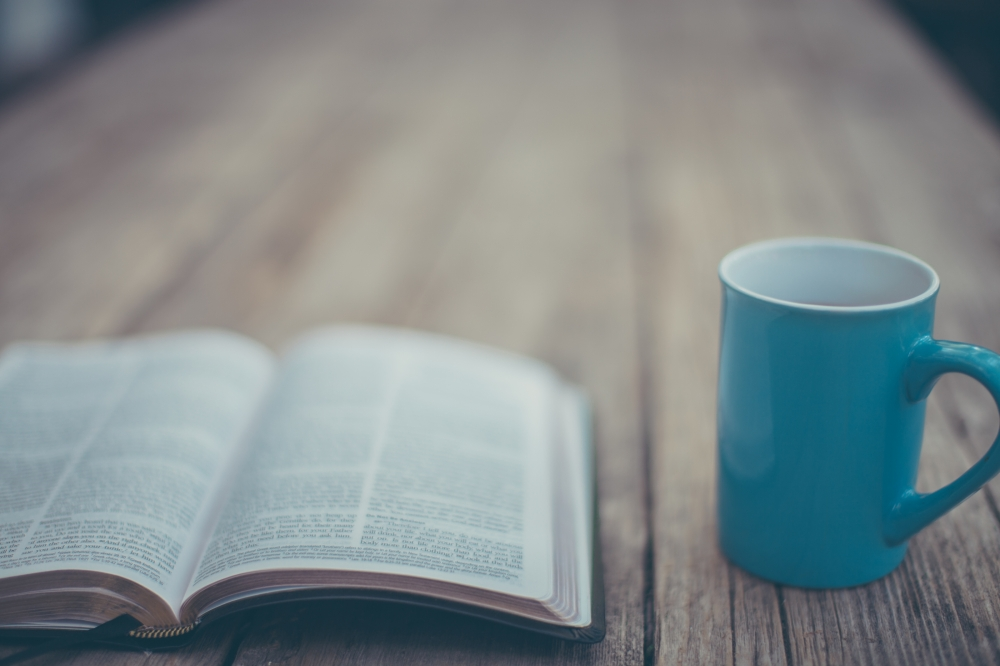 an open Bible lying on a table, next to a mug