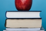 an apple on top of a stack of books