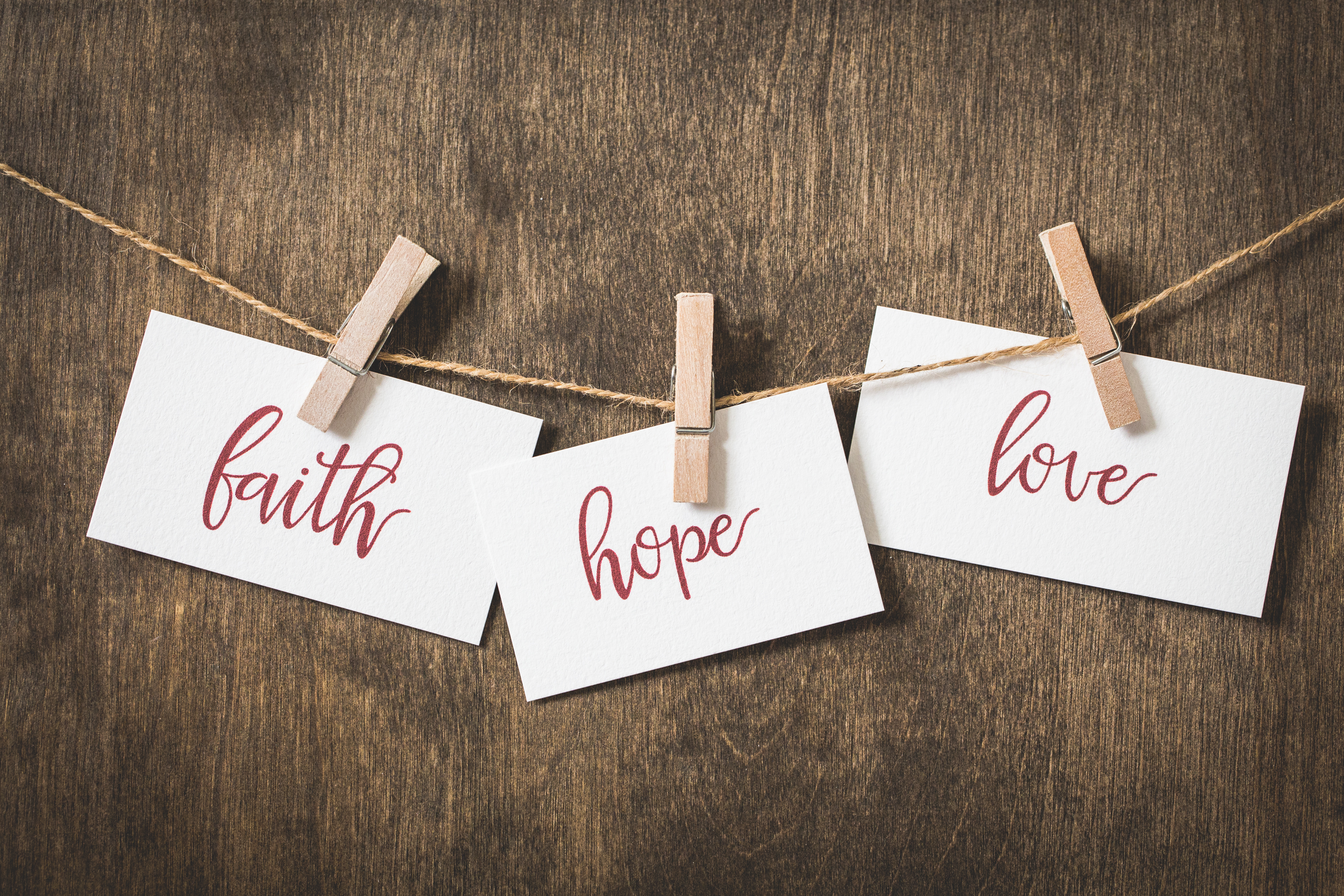 """faith, hope, love"" each word written on a card, strung on a line with clothes pins"