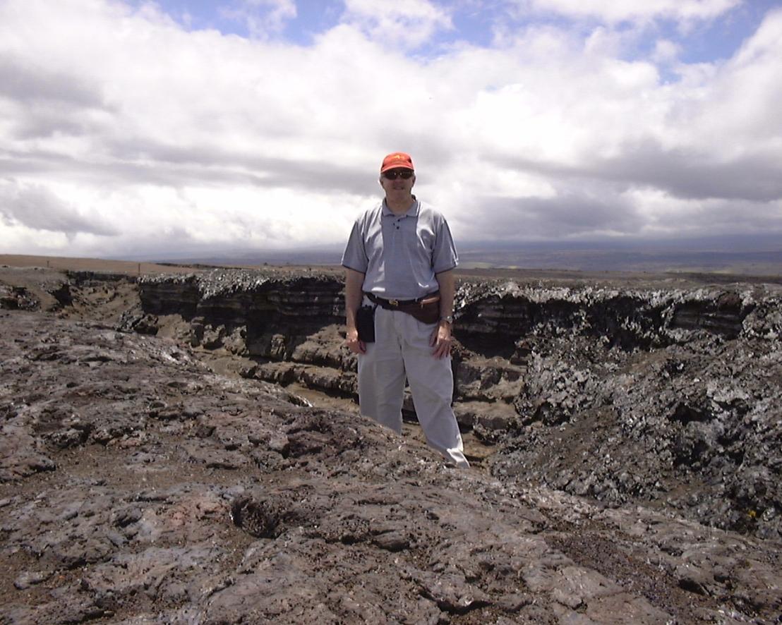 man standing on black rocks