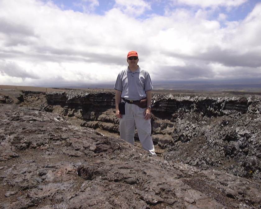 man standing on black rocks
