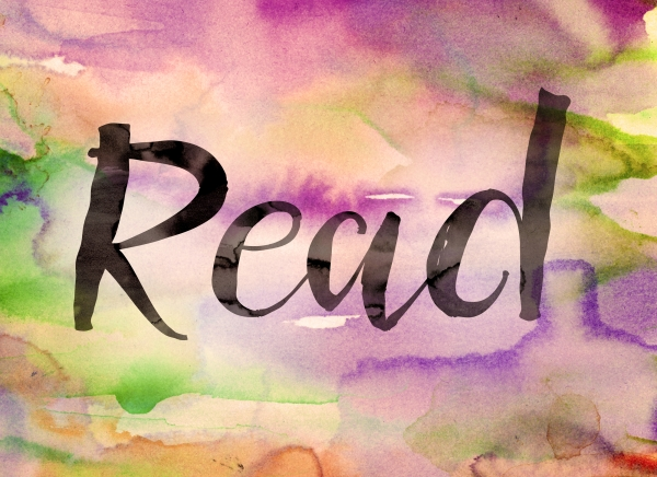 "The word ""Read"" written in black paint on a colorful watercolor washed background."