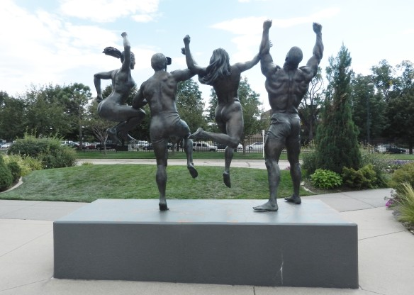 statue of four athletes raising arms