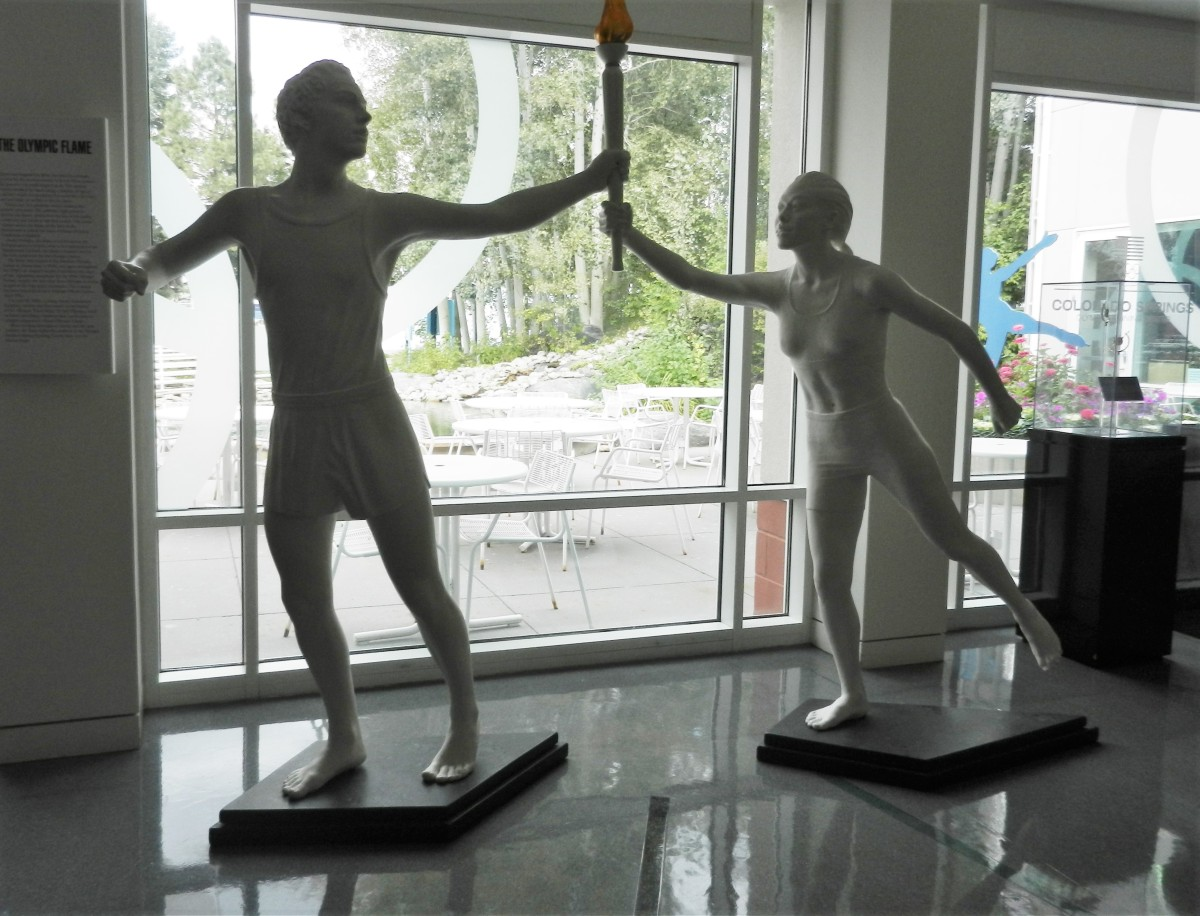 statues of runners passing a torch