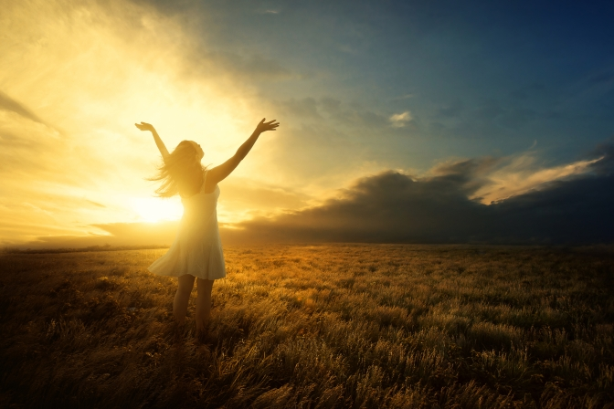 A woman lifts her arms in praise at sunset