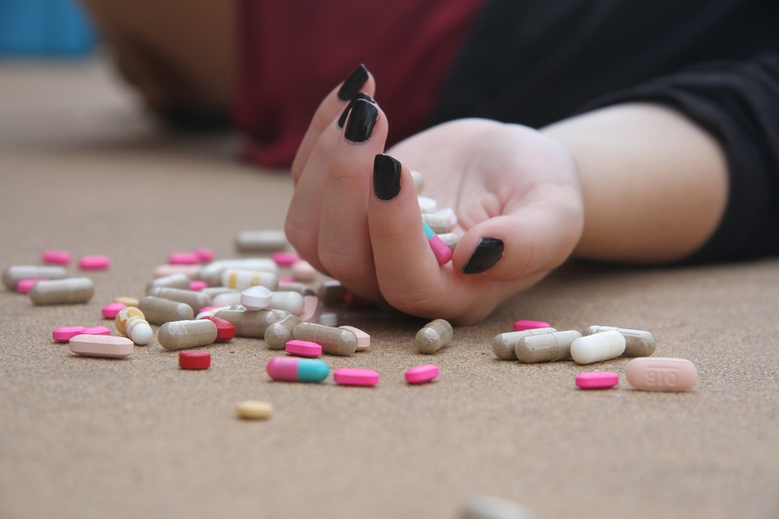 lying woman with palm full of pills