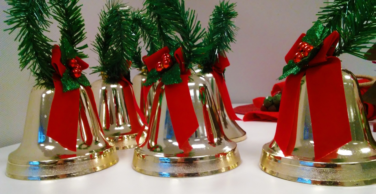 shiny gold bells decorated with red ribbon and greenery