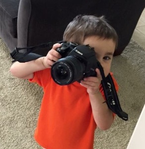 little boy with a big camera