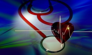 a stethoscope, a red heart and a heart ekg tracing