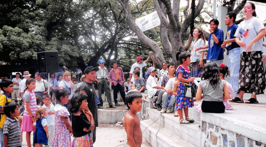 a group of children and adults watching people on a stage outdoors