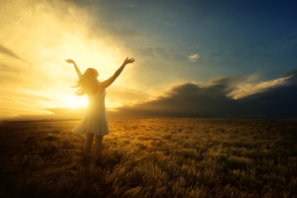 woman raising arms arms to the sky in a glow of light