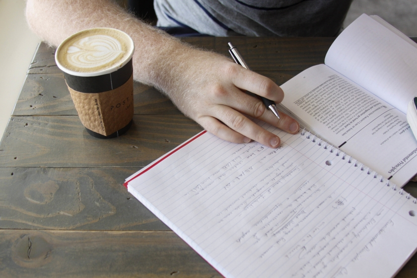 person writing in a spiral notebook