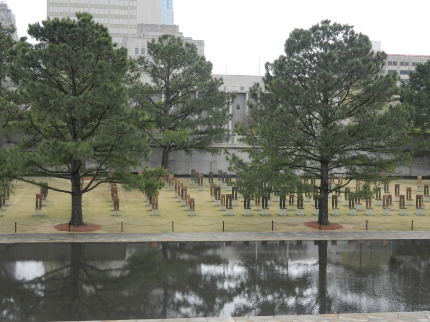 gold memorial chairs surrounded by trees at the Oklahoma National Memorial
