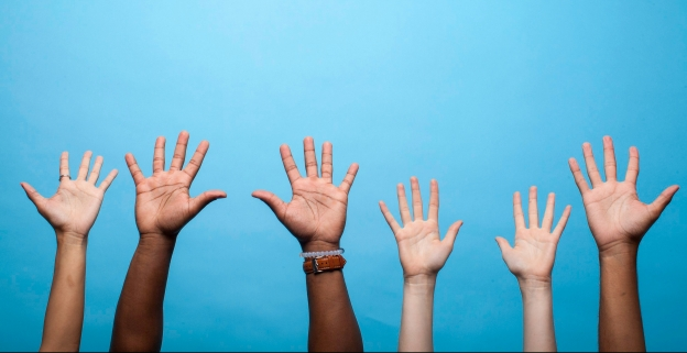 black and white person's' hands raised