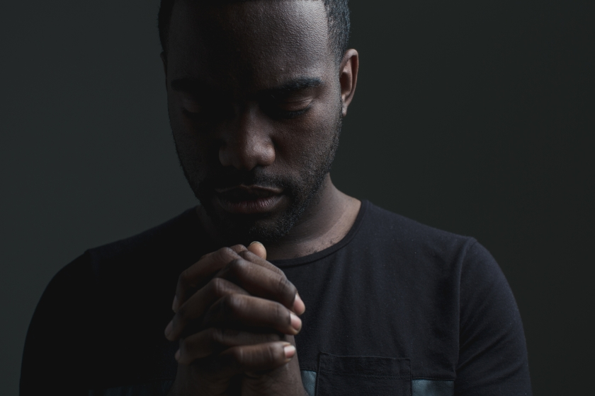 man with hands folded in prayer
