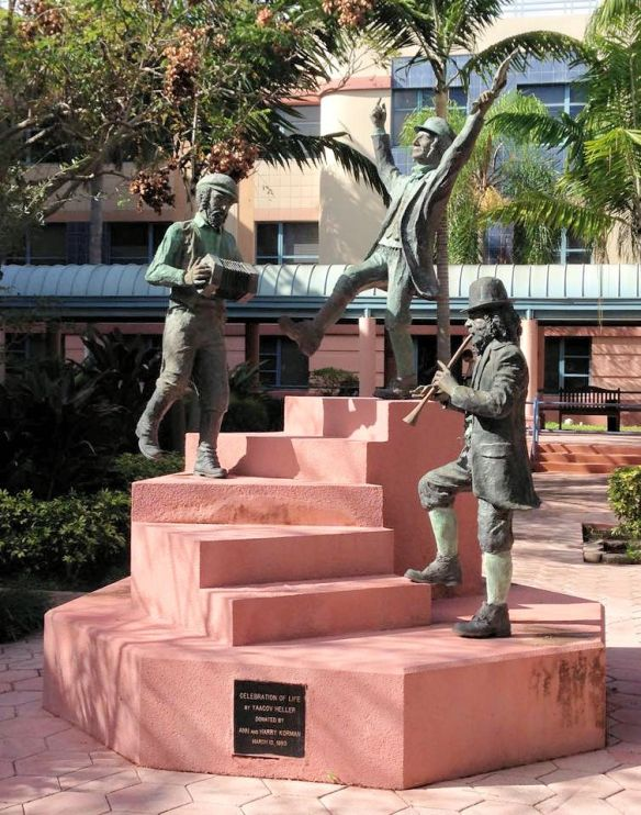 statue of 3 men dancing and playing instruments