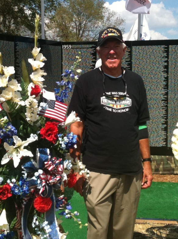 army veteran standing next to a floral bouquet at a memorial