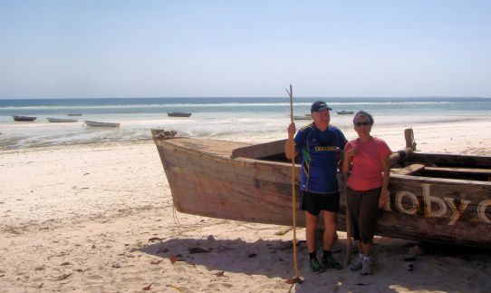 man and woman next to a wooden boat on a beach