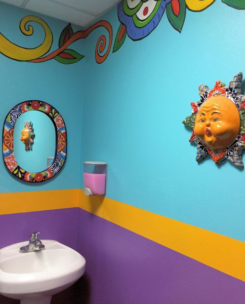 a sink with colorful wall decorations
