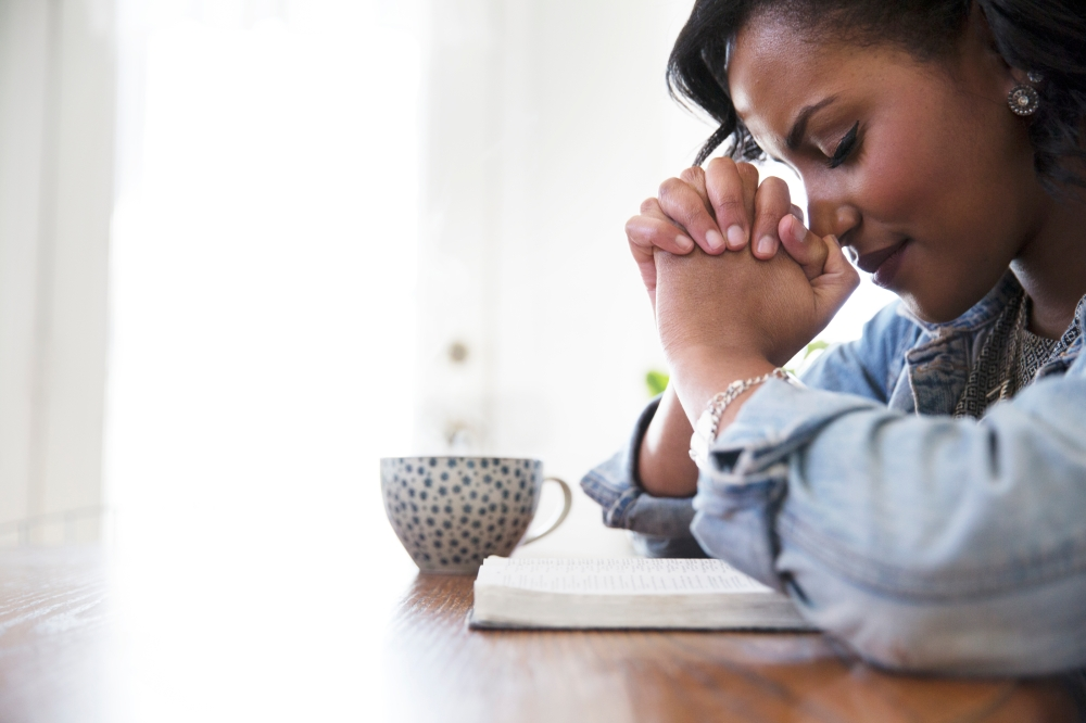 woman with hands bowed in prayer