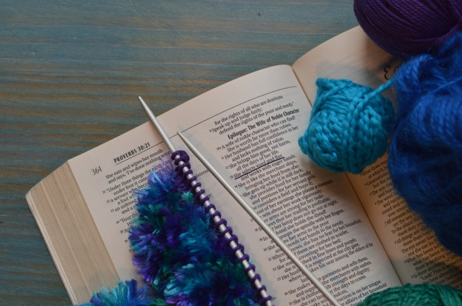 Bible open to Proverbs 31 with yarn and knitting needles