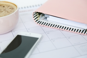 a smartphone lying on a calendar page with a planner and cup of coffee