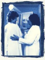 a woman having a mammogram done by a technician
