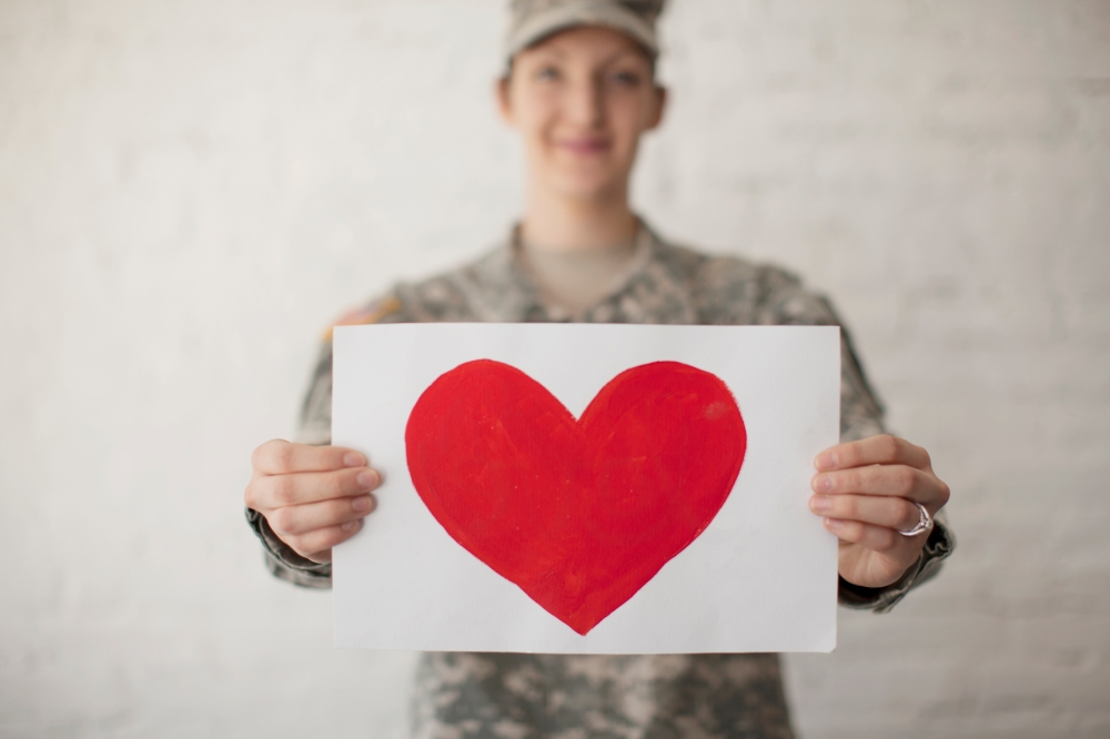 a female soldier holding a red heart drawn on white paper